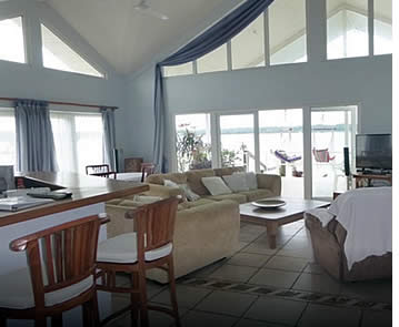 Expansive living area including open plan kitchen plus living room with glass windows, access to terrace and water views